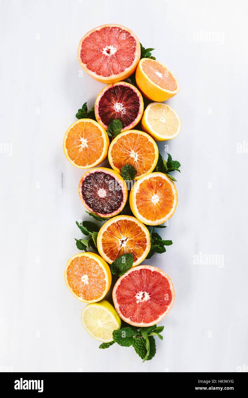Citrus orange, grapefruit and mint display on marble. - Stock Image