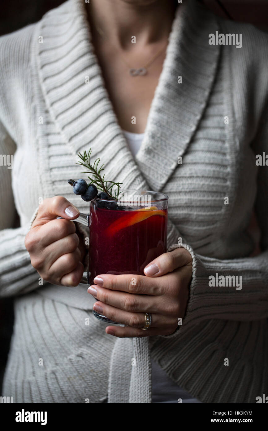 A woman is photographed with a glass of blueberry hot toddy in her hand - Stock Image