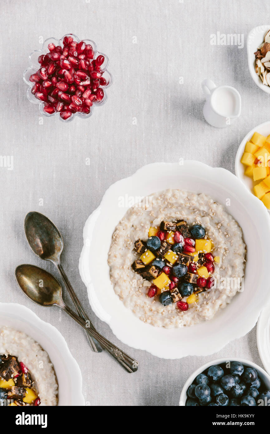 A bowl of steel cut oats topped off with fruits and brownie bits is photographed from the top view. - Stock Image