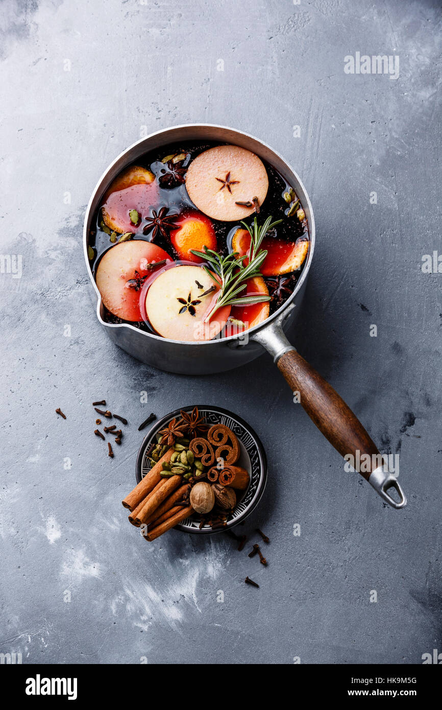 Mulled wine hot drink with citrus, apple and spices in aluminum casserole on concrete background Stock Photo