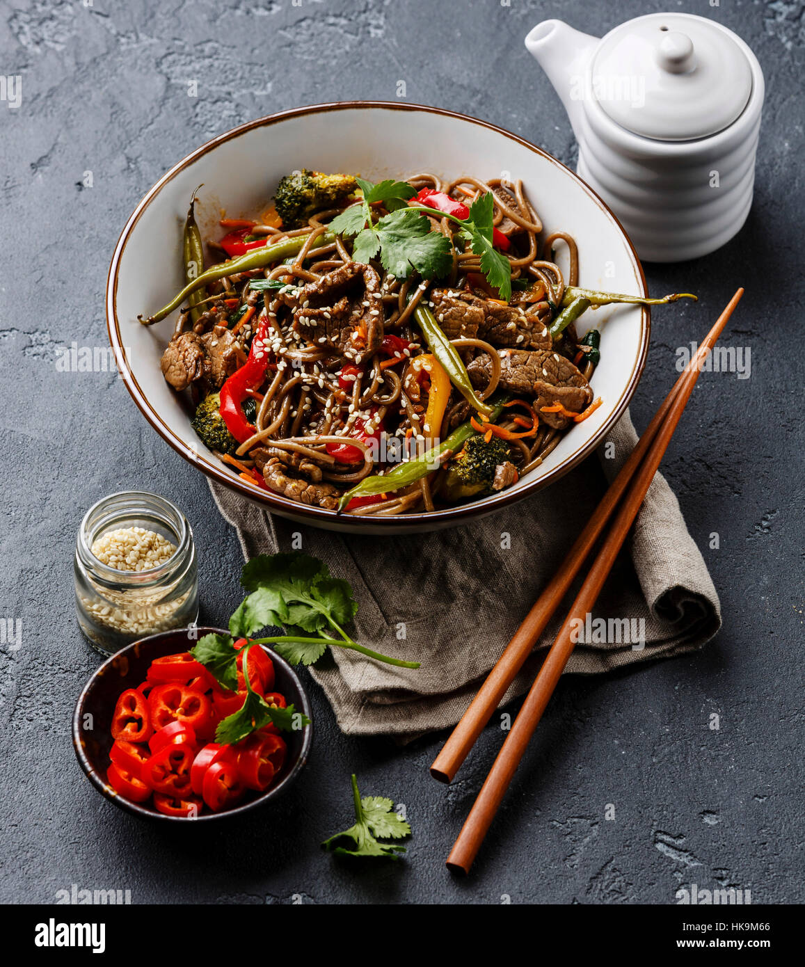 Stir fry noodles soba with beef and vegetables in bowl on dark stone background - Stock Image