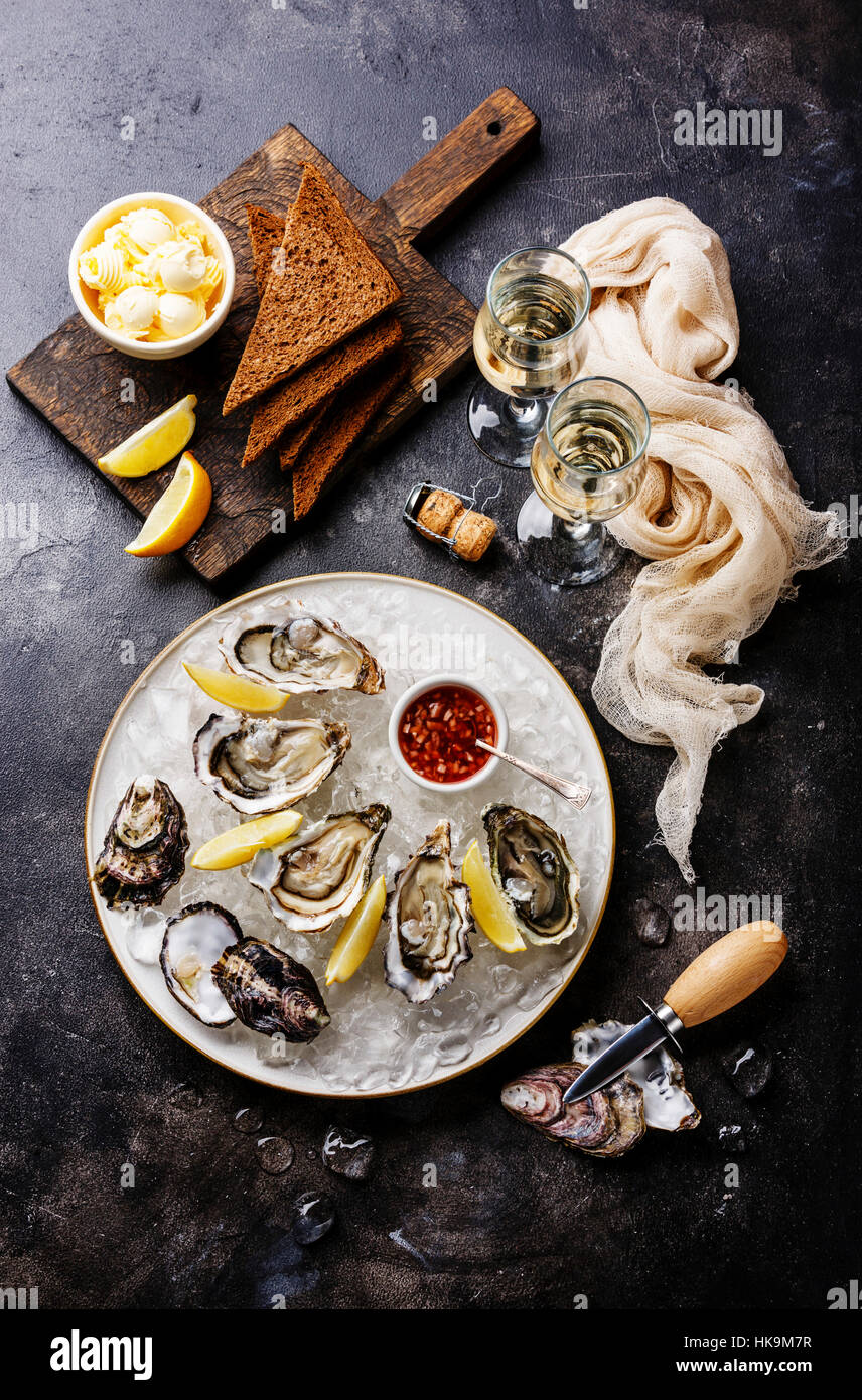 Open Oysters with bread and butter and champagne on dark texture background - Stock Image