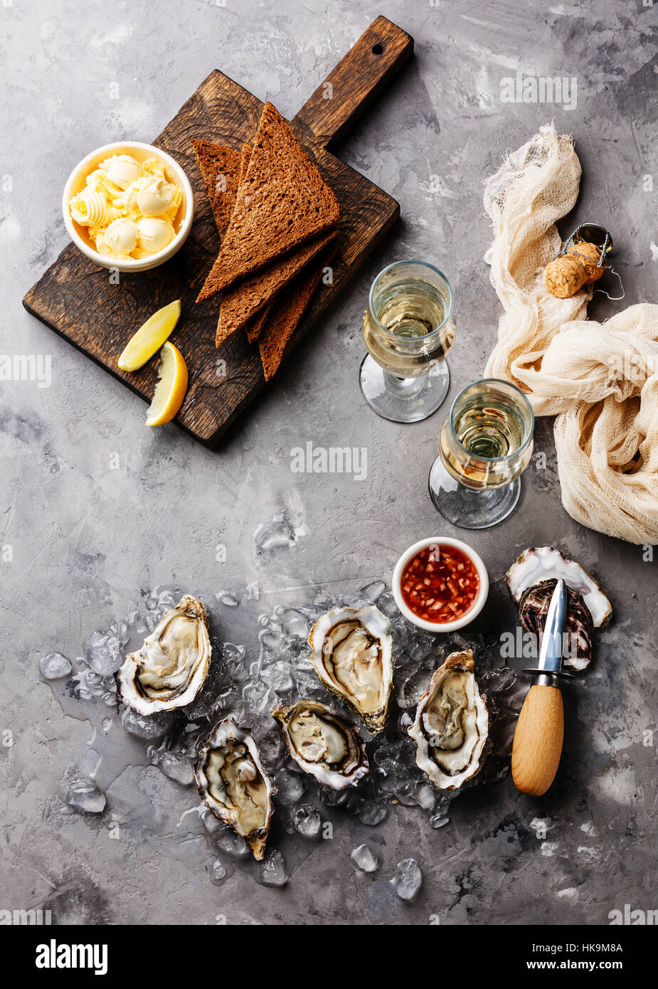 Open Oysters with bread and butter and champagne on gray concrete texture background - Stock Image
