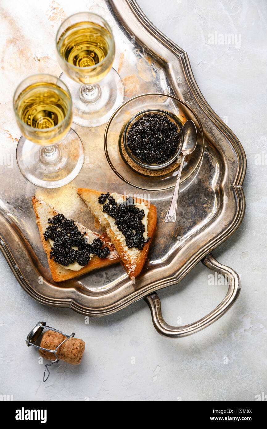 Sturgeon black caviar, sandwiches and champagne on silver tray - Stock Image