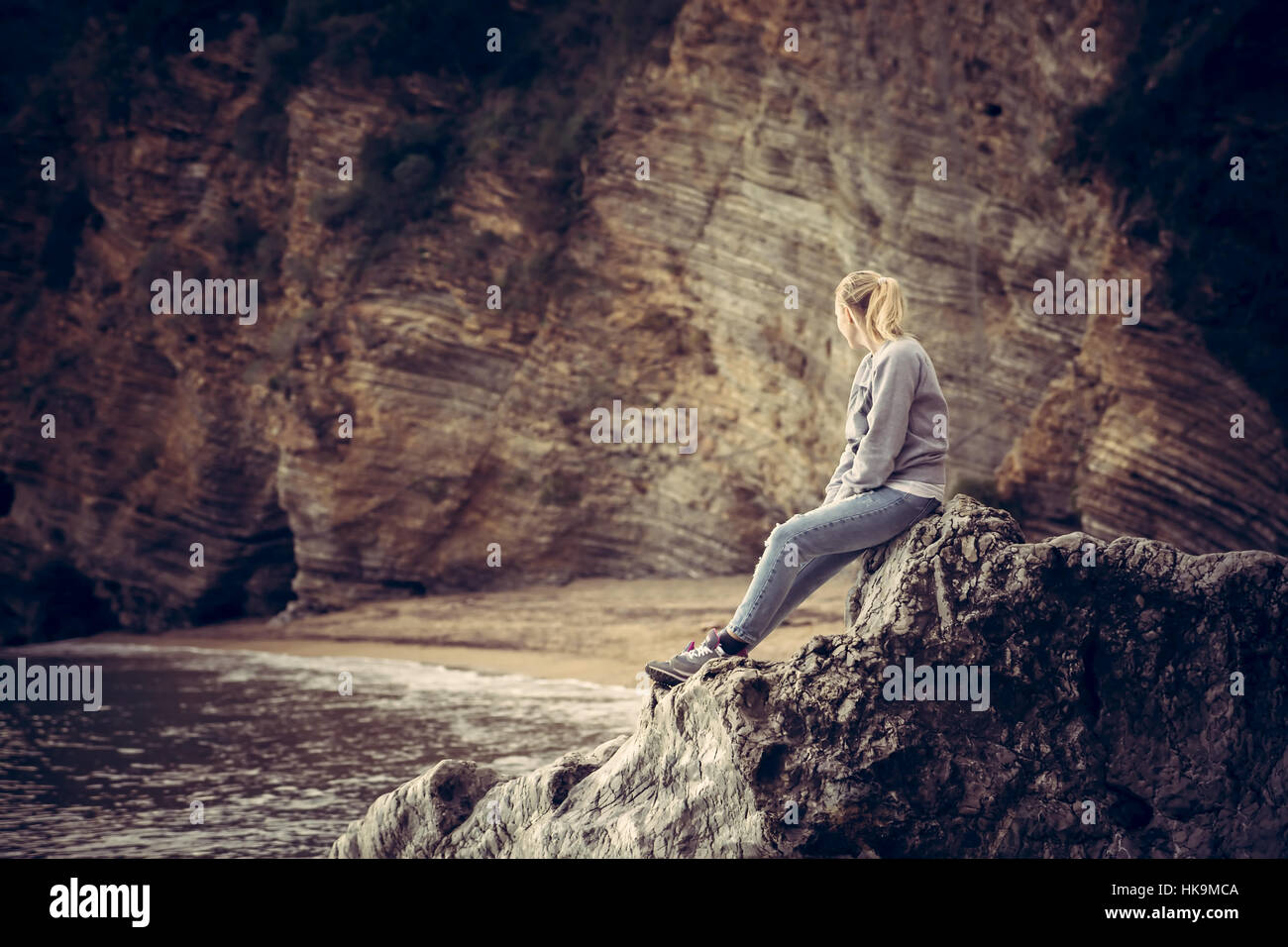 Pensive lonely young woman traveler relaxing on a big cliff stone on the beach looking at wild mountain scenery - Stock Image