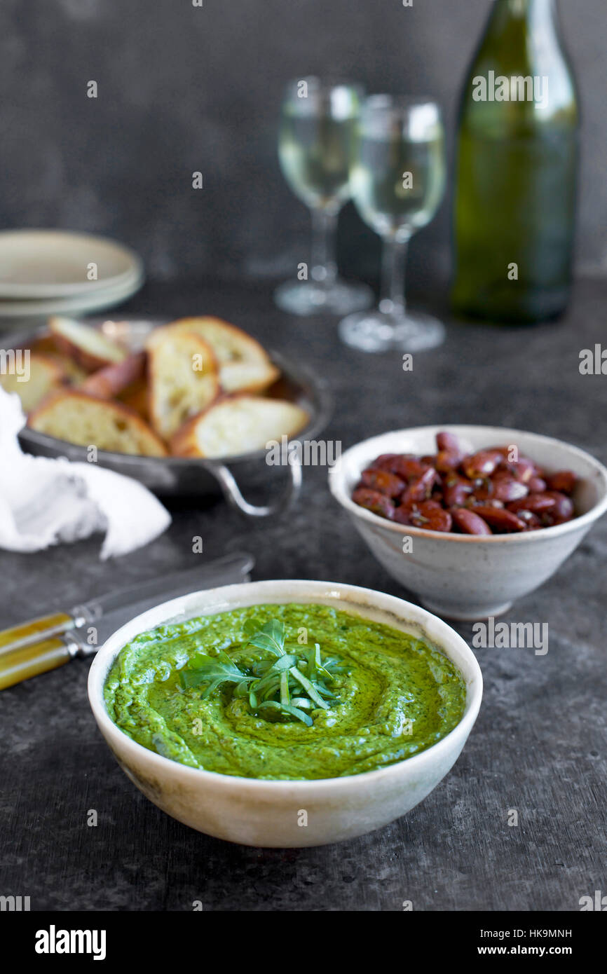 Arugula Chive Basil Pesto served in a ceramic bowl with crostini, almonds and wine.  Photographed fron front view - Stock Image