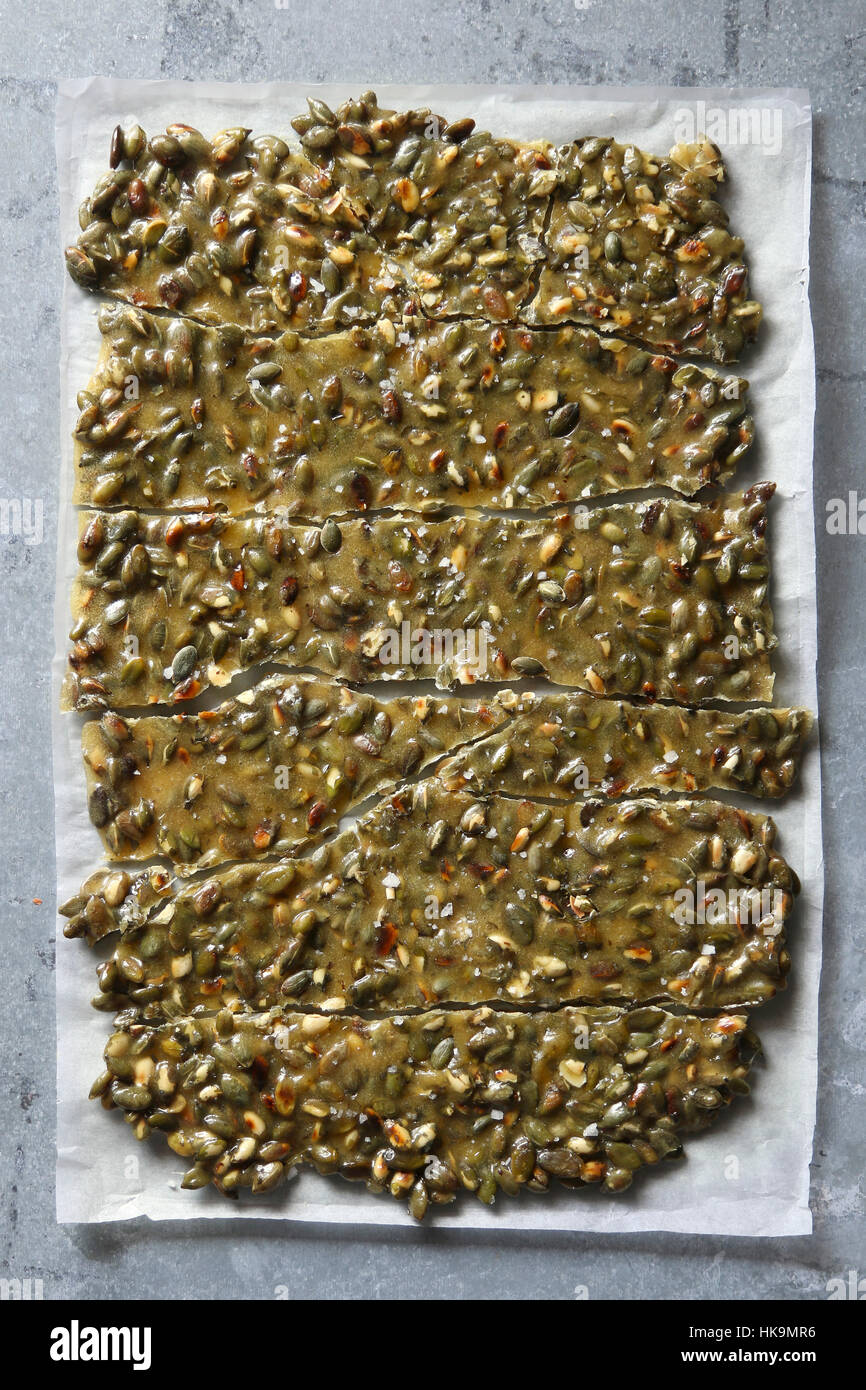Toasted Pumpkin seed brittle on a parchment paper.Top view - Stock Image