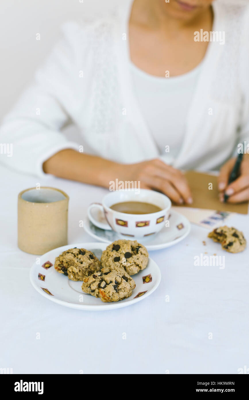 A woman writing a letter while having oatmal cookies and coffee. - Stock Image