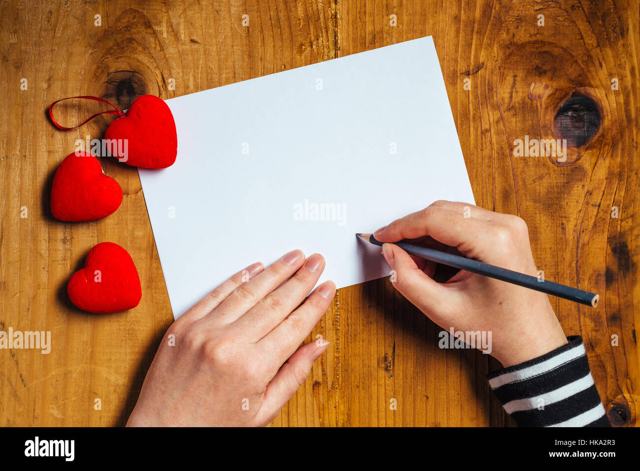 Woman writing love letter or romantic poem for Valentines day, top view - Stock Image