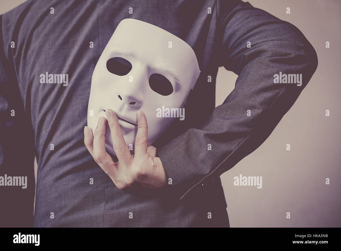 Business man carrying white mask to his body indicating Business fraud and faking business partnership. - Stock Image