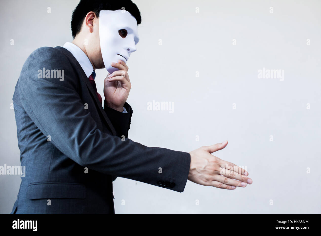 Business man giving dishonest handshake hiding in the mask - Business fraud and hypocrite agreement. - Stock Image