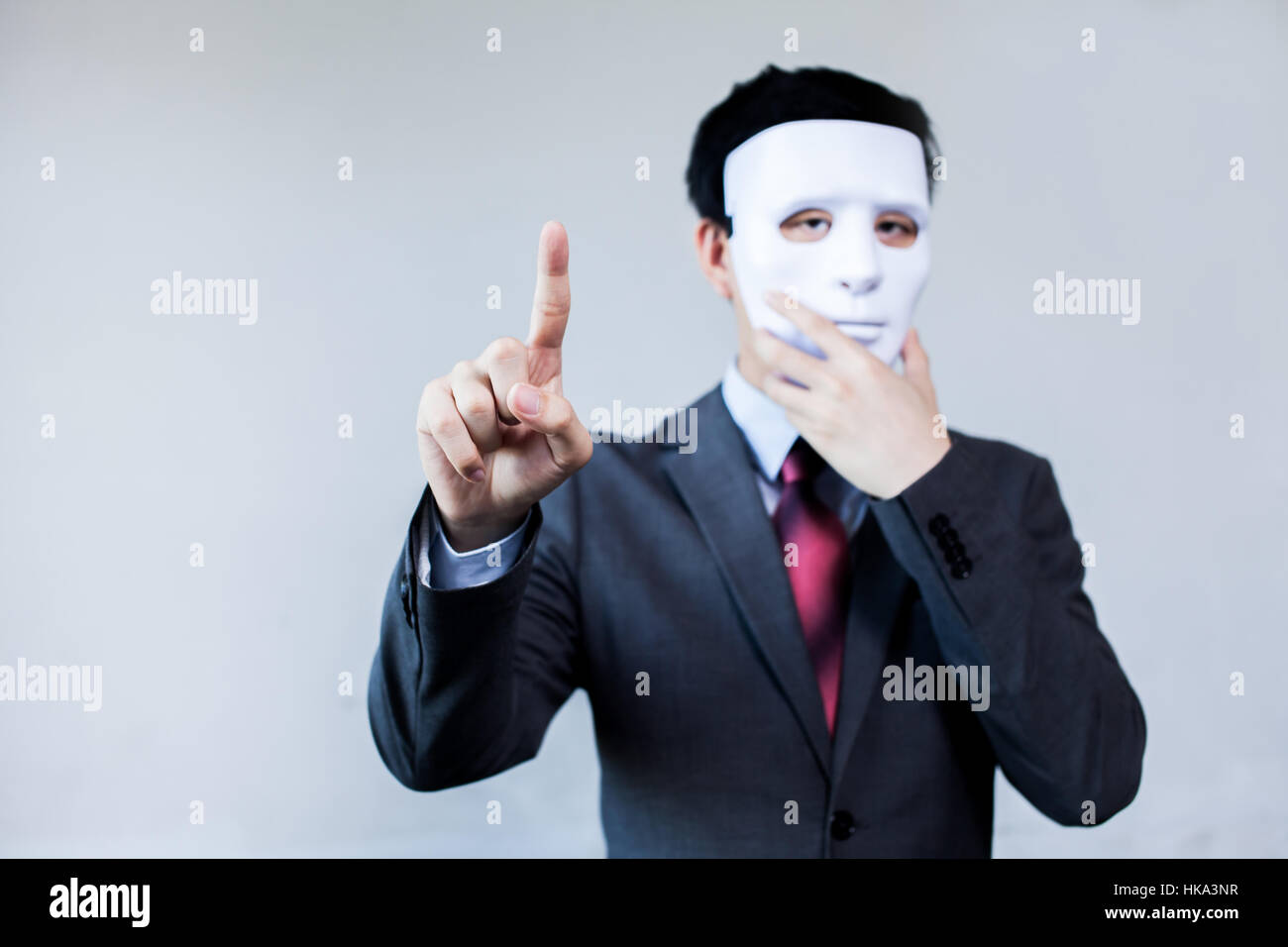 Anonymous businessman in mask hiding himself touching on virtual screen - with copyspace. - Stock Image