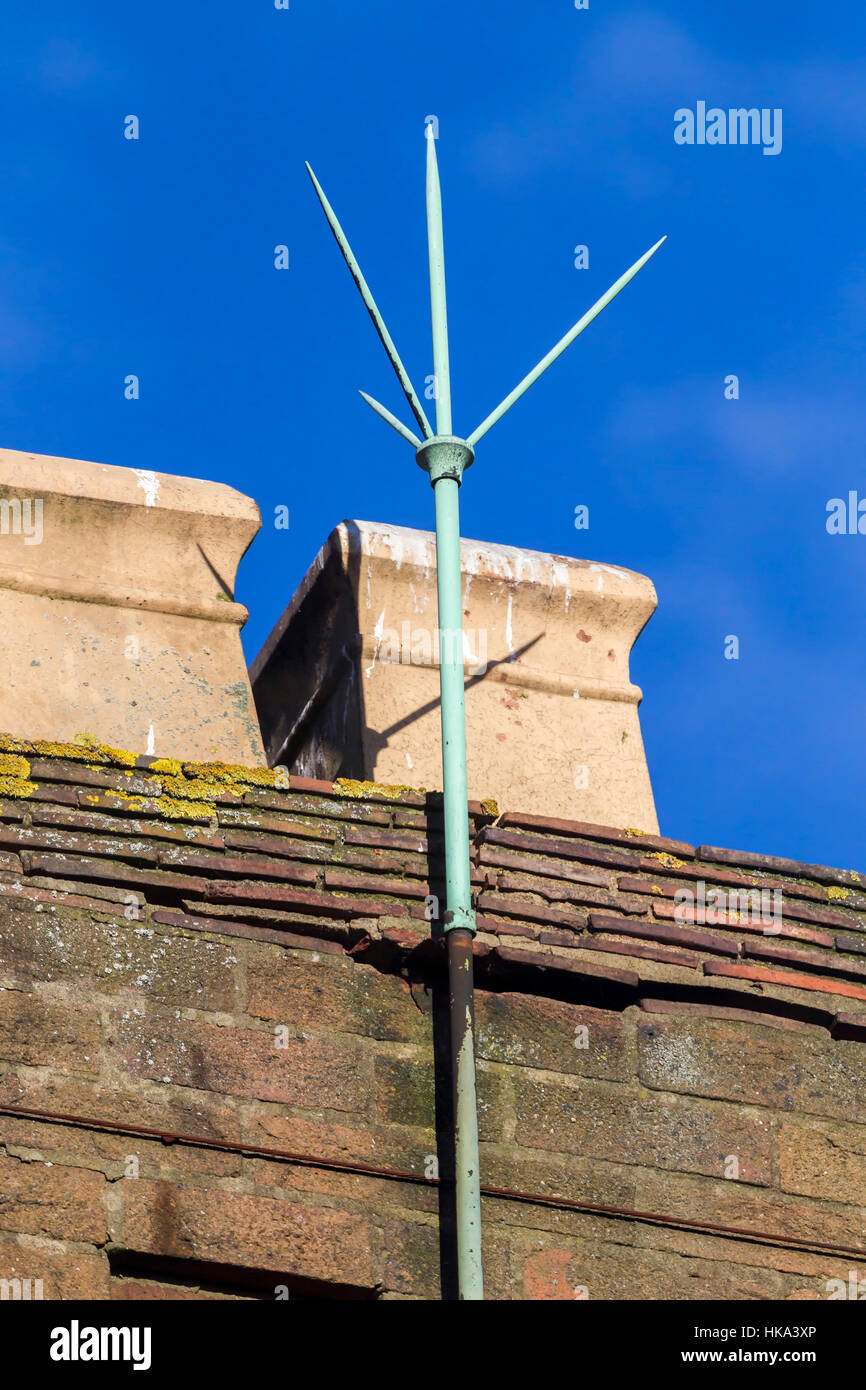 Lightening conductor on chimney pot against a blue sky. - Stock Image