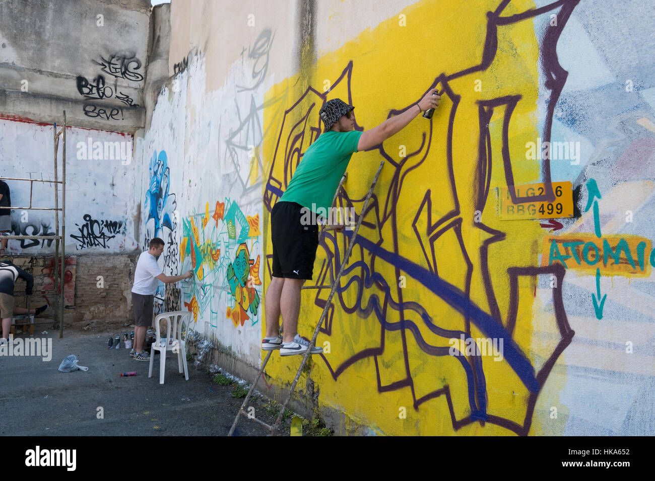 A man painting graffiti on the wall, Limassol, Cyprus Stock Photo ...