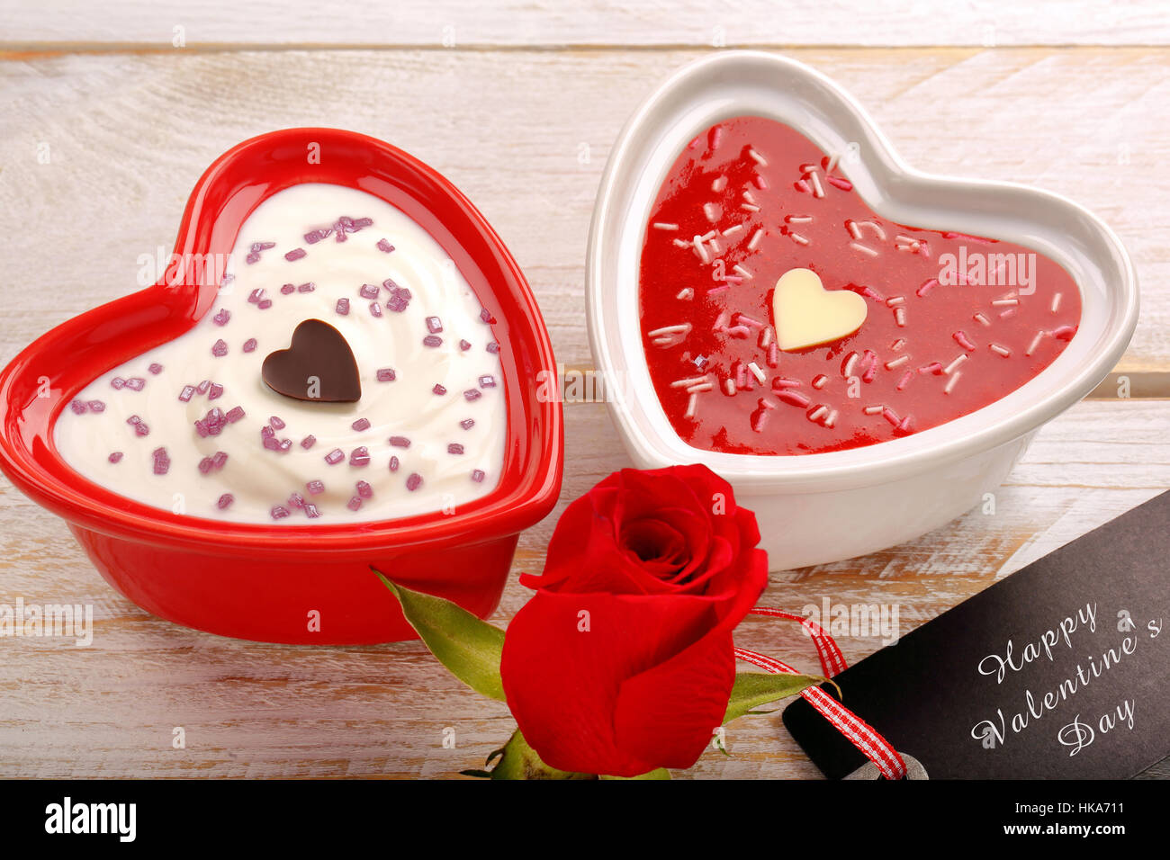 Sweet dessert for Valentines Day with card for text on wooden background - Stock Image