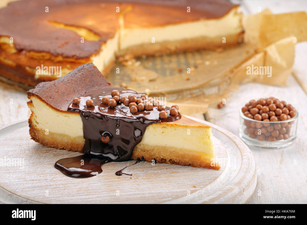 Cheesecake slice with melted chocolate and chocolate balls - Stock Image
