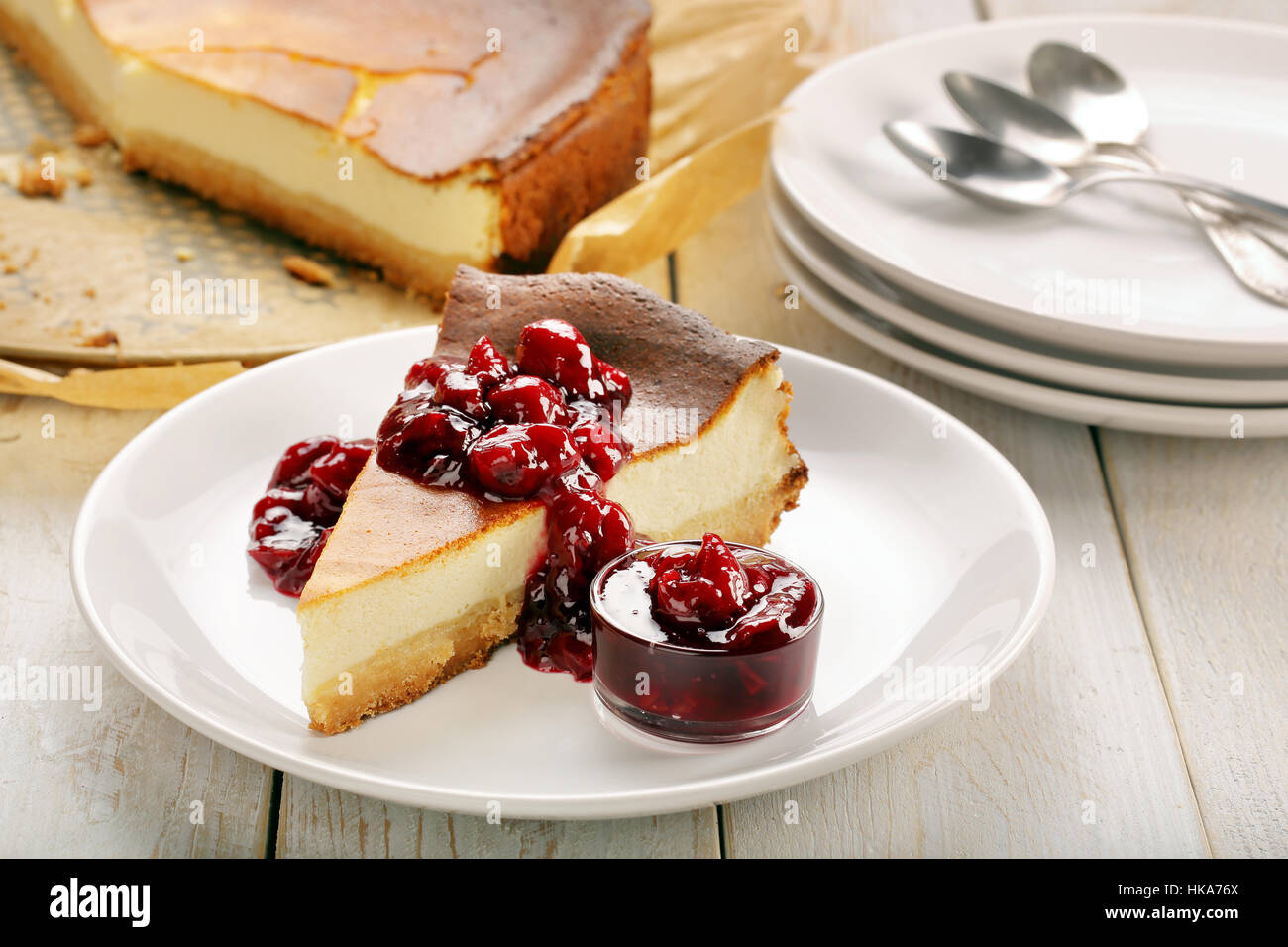Cheesecake slice with cherry jam on wooden background - Stock Image