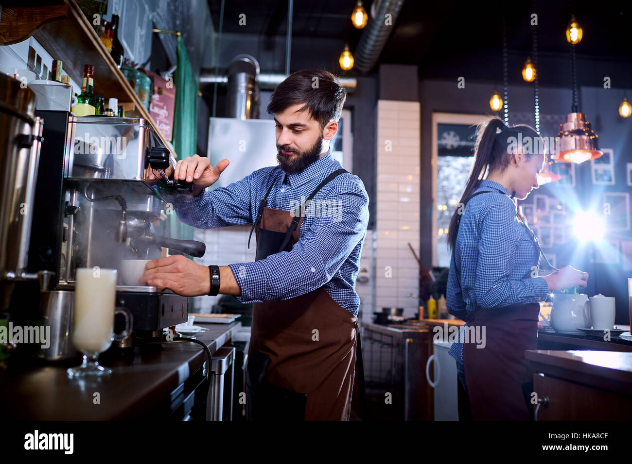 Barman barista uniform making coffee tea cocktails in the bar, r - Stock Image