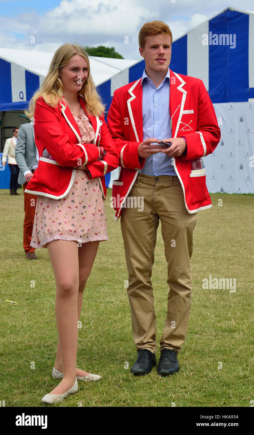Young couple wearing red rowing blazers stand on the