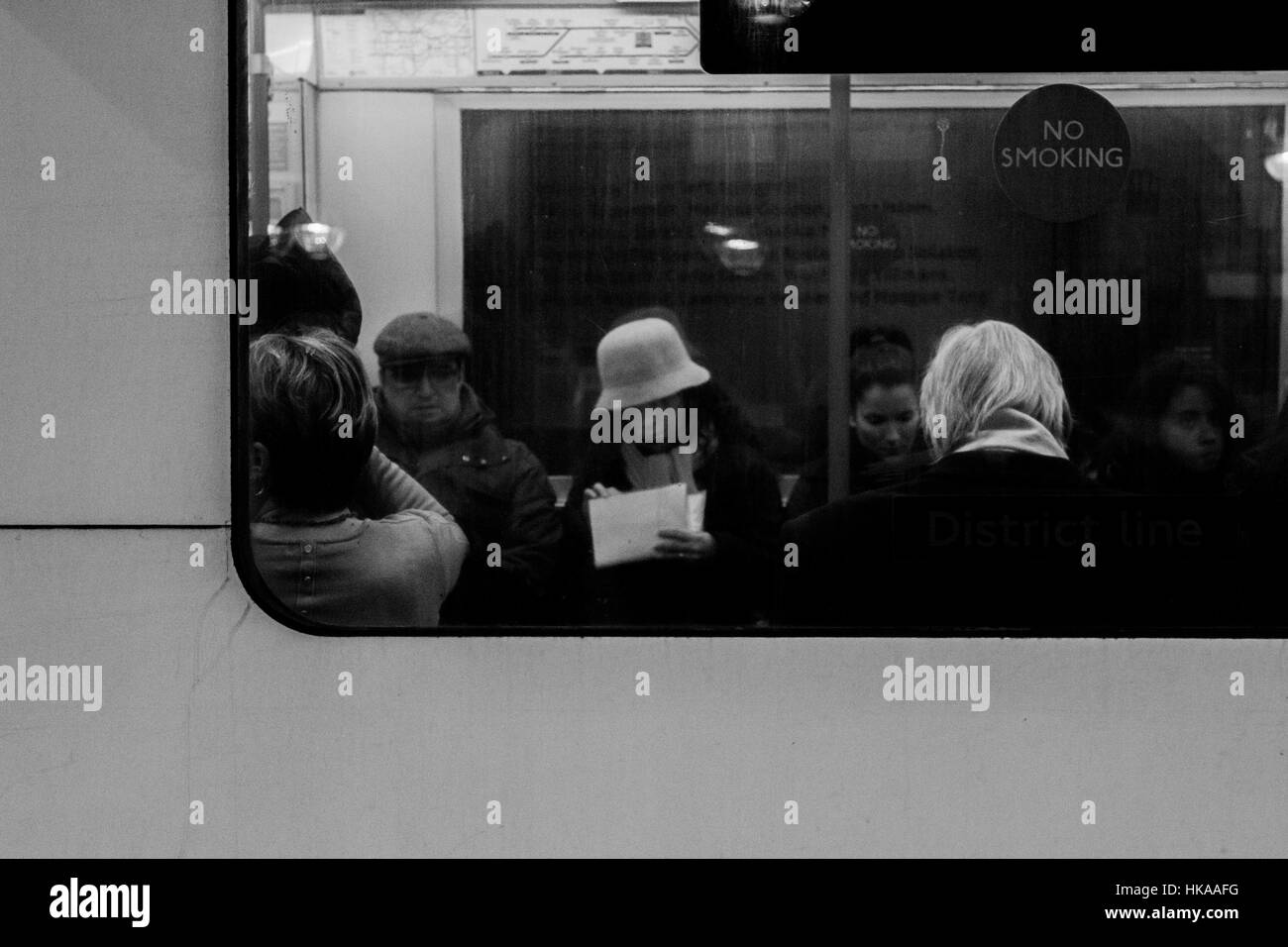 Commuters travel on the tube. London, UK. - Stock Image