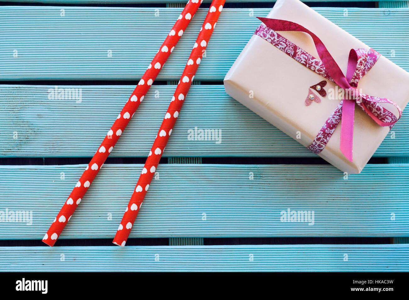 Overhead of handmade gift with vibrant bow tie and red paper straws with hearts shape on blue wooden background Stock Photo