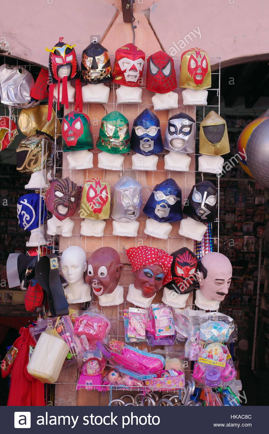 Outdoor market shot Mexico display of face masks in style used by professional Mexican wrestlers bright sun midday. - Stock Image