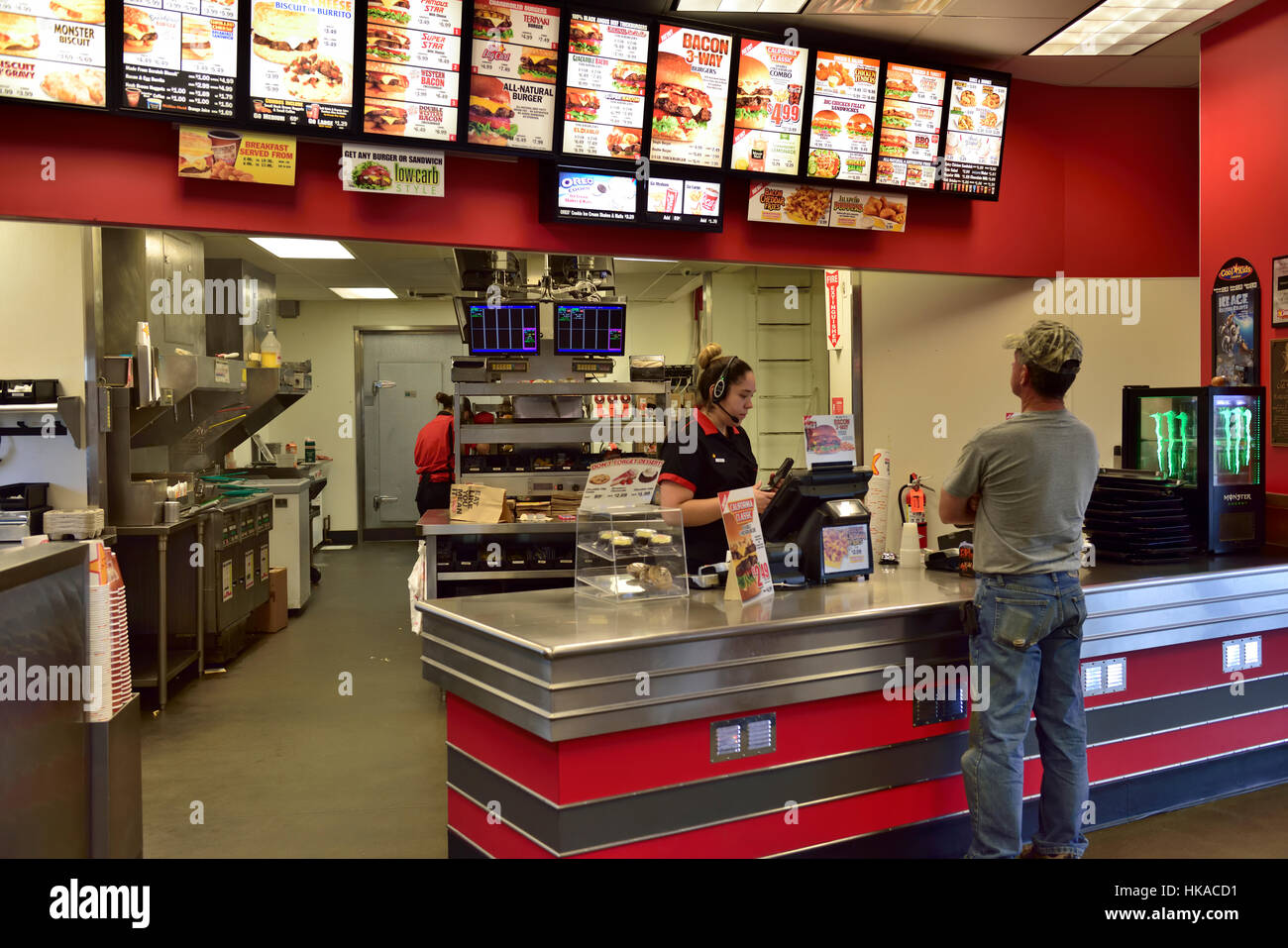 Waitress serving customer inside American fast food restaurant Carl's Jr, Arizona - Stock Image