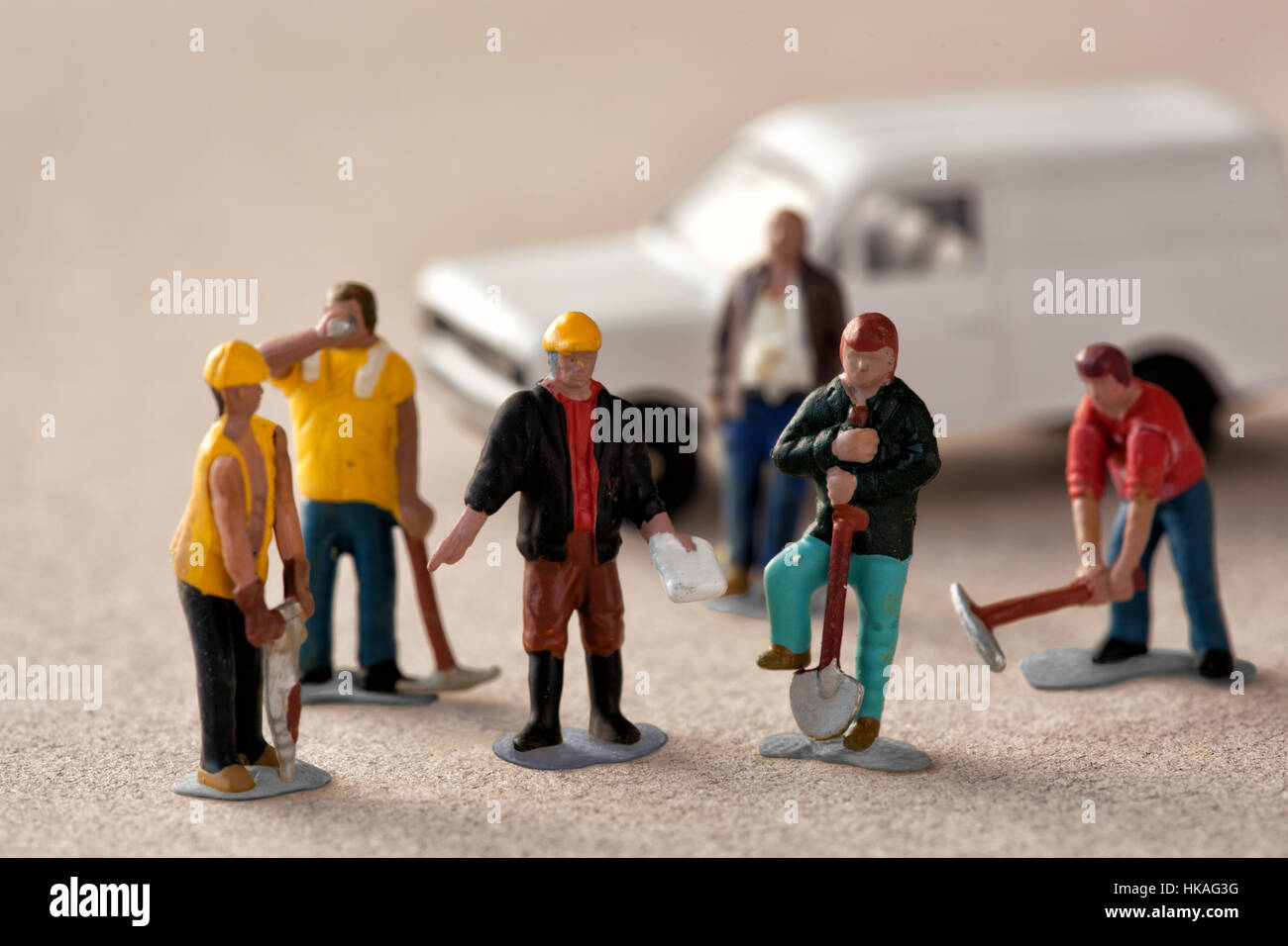 Miniature workmen stand around their foreman on an outdoor site with a van - Stock Image