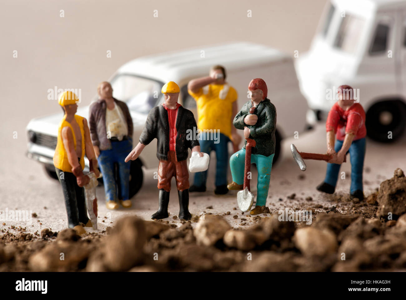 Miniature model workmen with their foreman and white vans - Stock Image