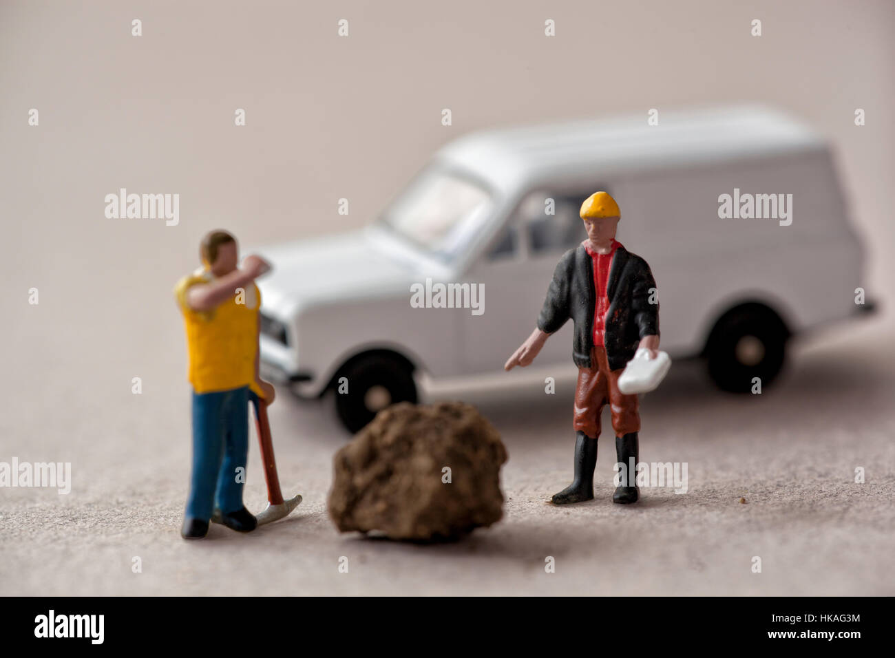 Miniature model supervisor and workman with a lump of earth and white van - Stock Image
