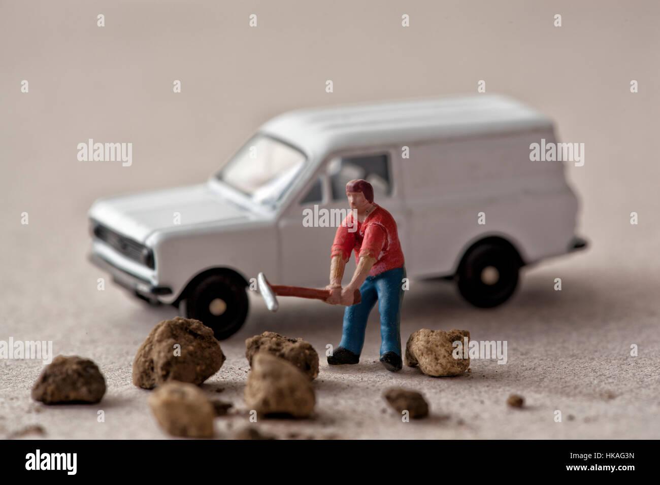 Miniature model workman hammers rocks next to a white van - Stock Image