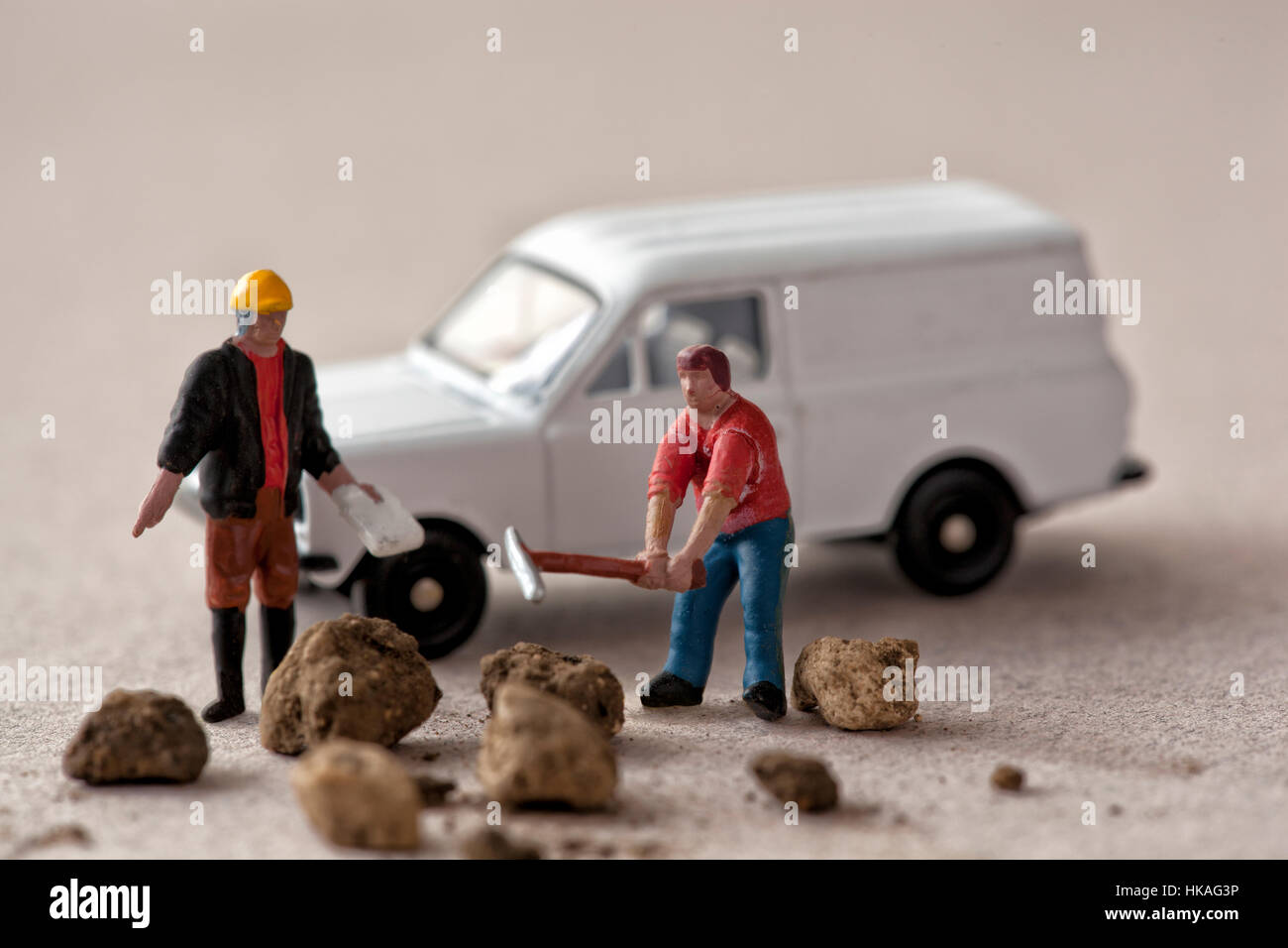 Miniature construction supervisor and worker with lumps of earth and white van - Stock Image