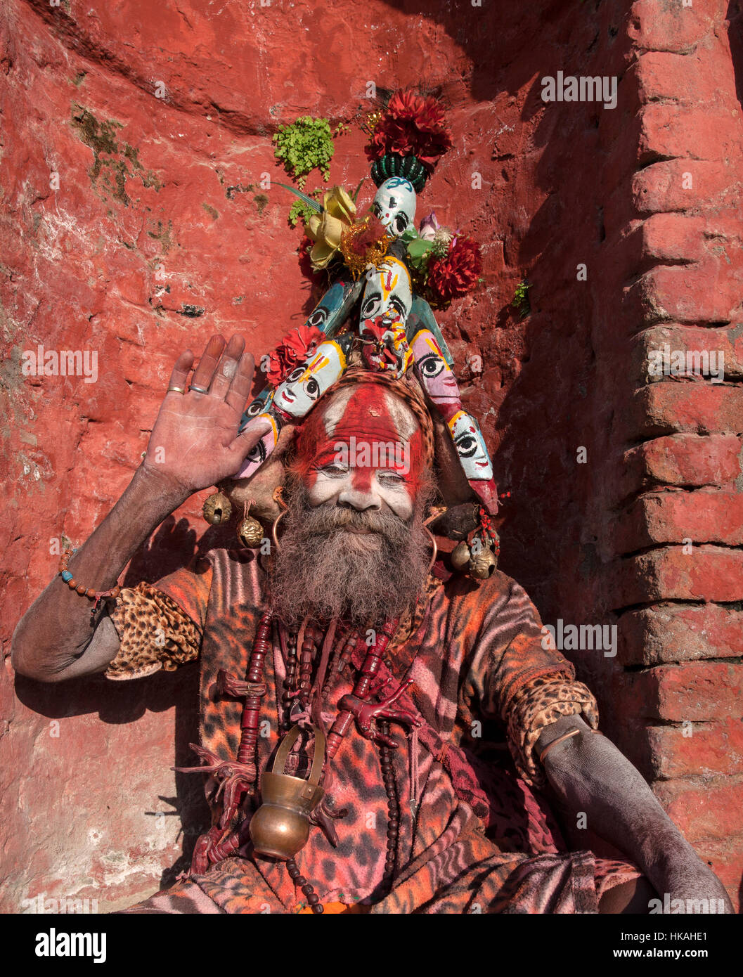 Holy man or sadhus at Pashupatinath Kathmandu Nepal. The mans face is painted red and white he has a headdress and Stock Photo