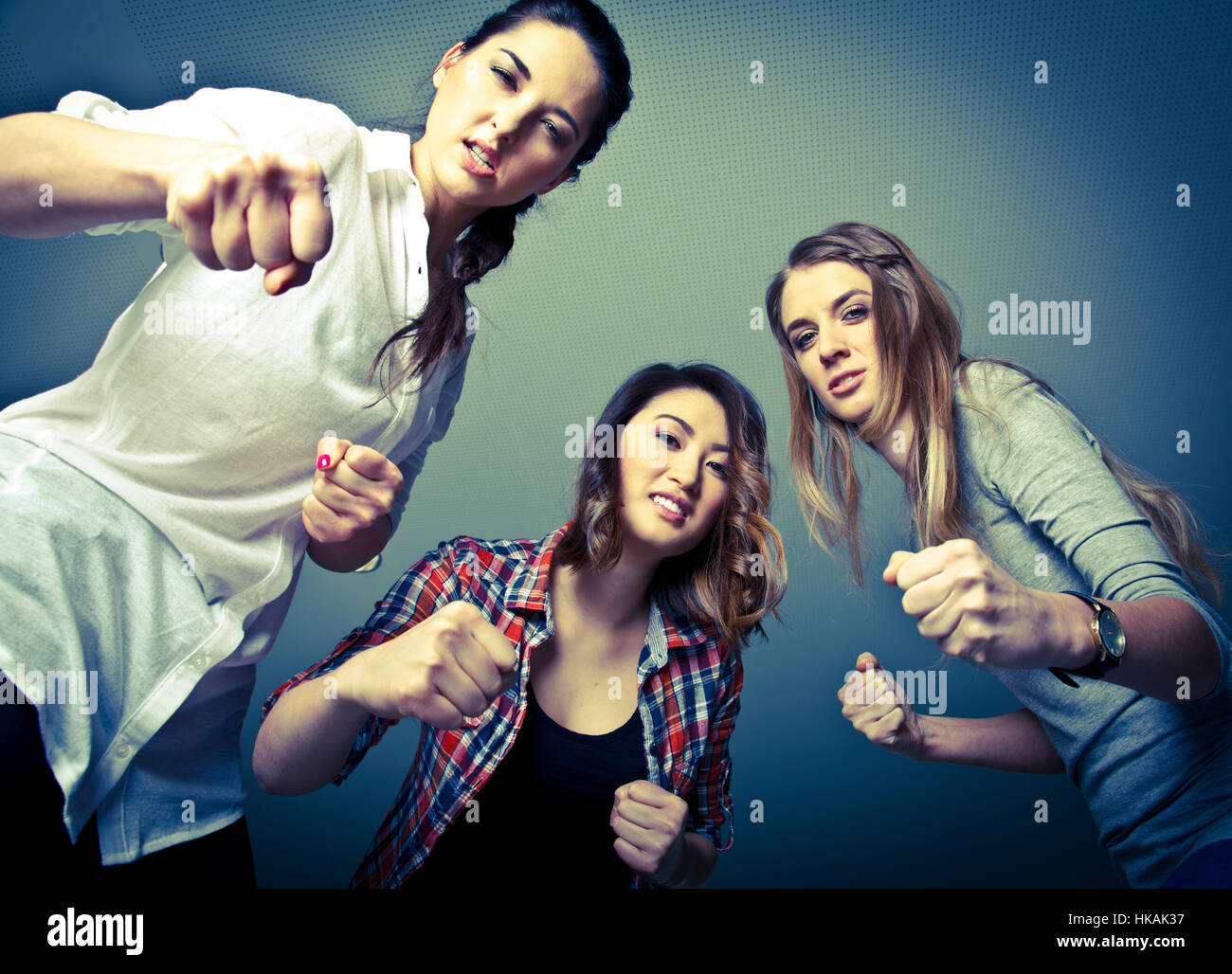 Drei böse Mädchen drohem ihrem Opfer mit Schlägen Stock Photo
