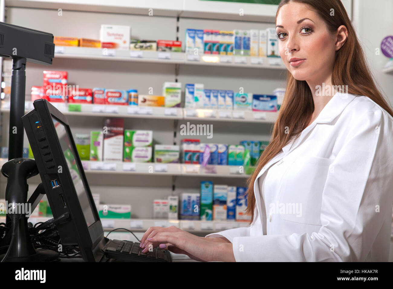 Female pharmacist searches medicine holding a prescription in her hand - Stock Image