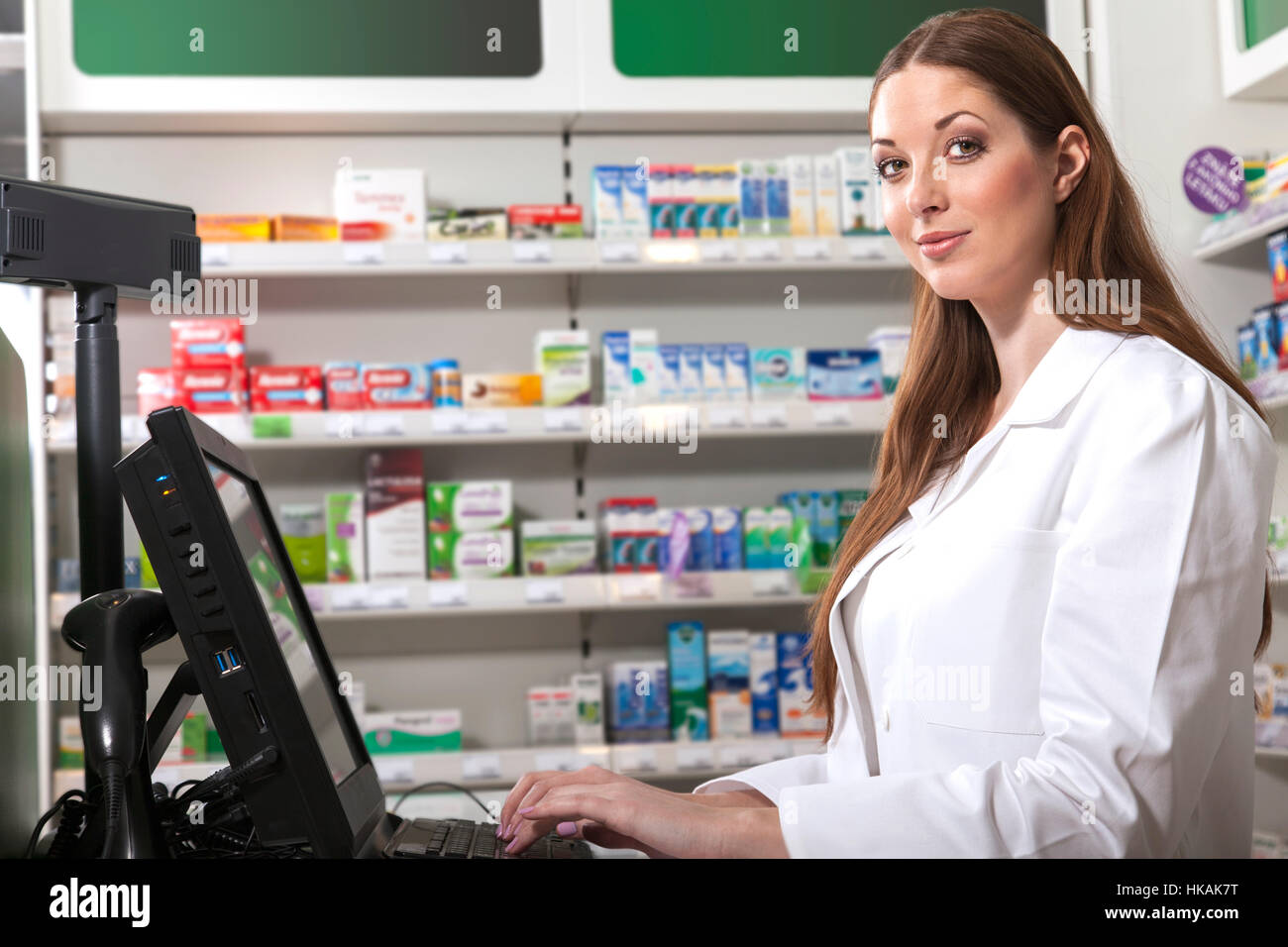 Female friendly pharmacist at the cash desk computer looks at the camera - Stock Image