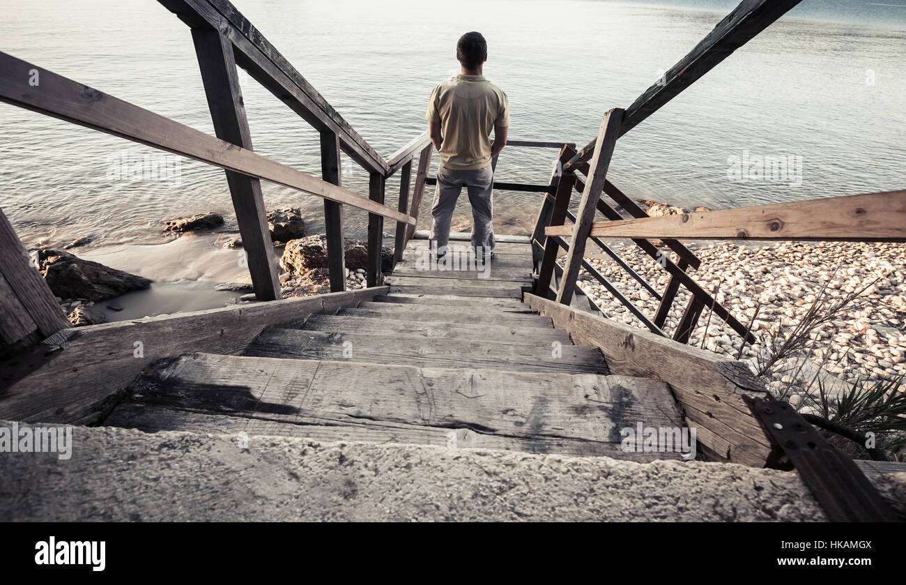 Young man stands on old wooden stairway going down to the sea coast. Vintage toned photo, old style photo filter Stock Photo