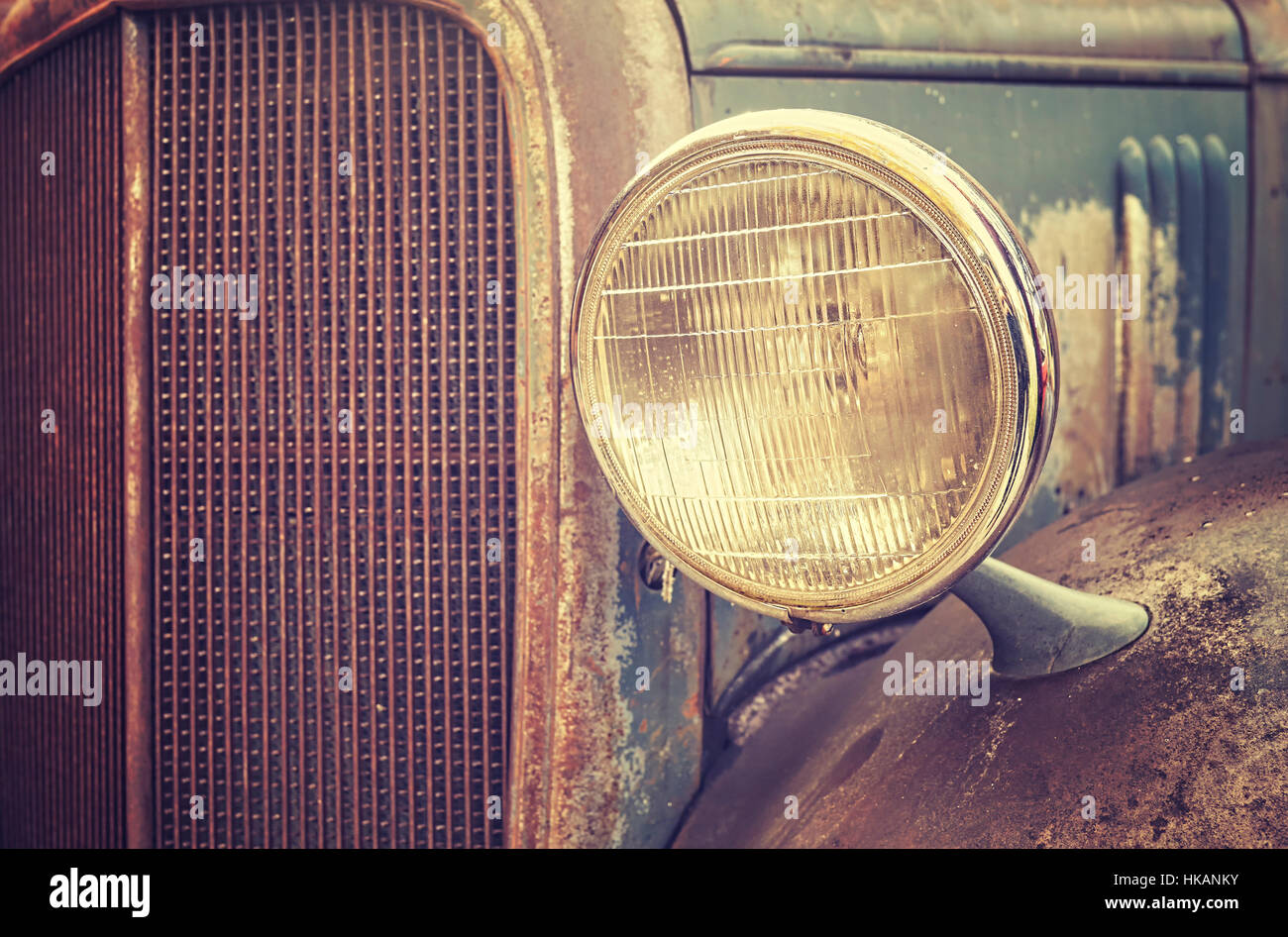 Color toned close up picture of an old rusty car headlamp, selective focus. - Stock Image