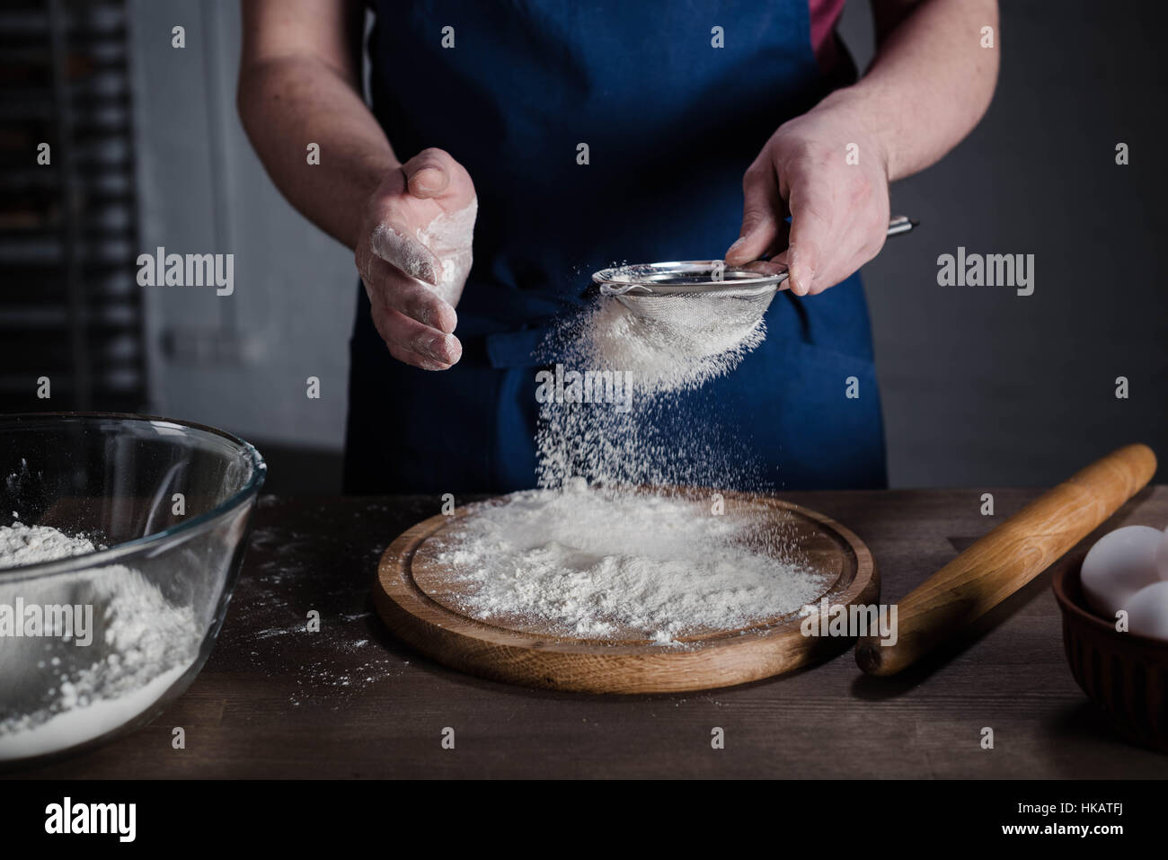 Baker sifting flour in the bakery, cropped shot - Stock Image