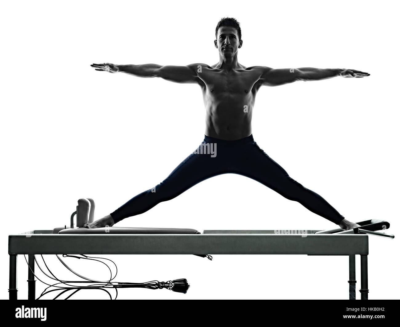 one caucasian man exercising pilates reformer exercises fitness in silhouette isolated on white backgound - Stock Image