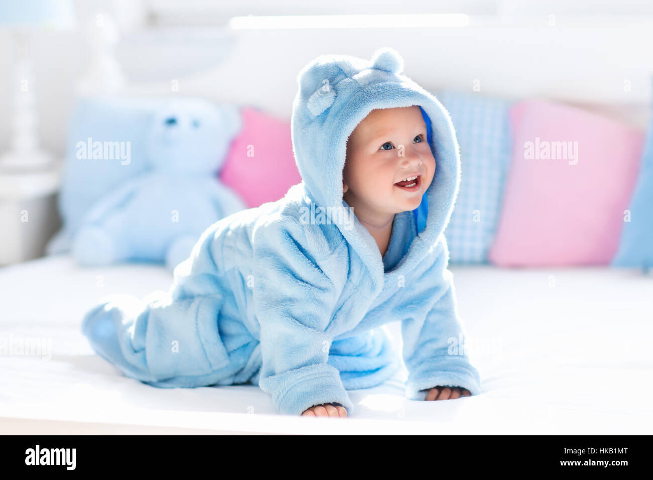 Cute happy laughing baby in soft bathrobe after bath playing on ...
