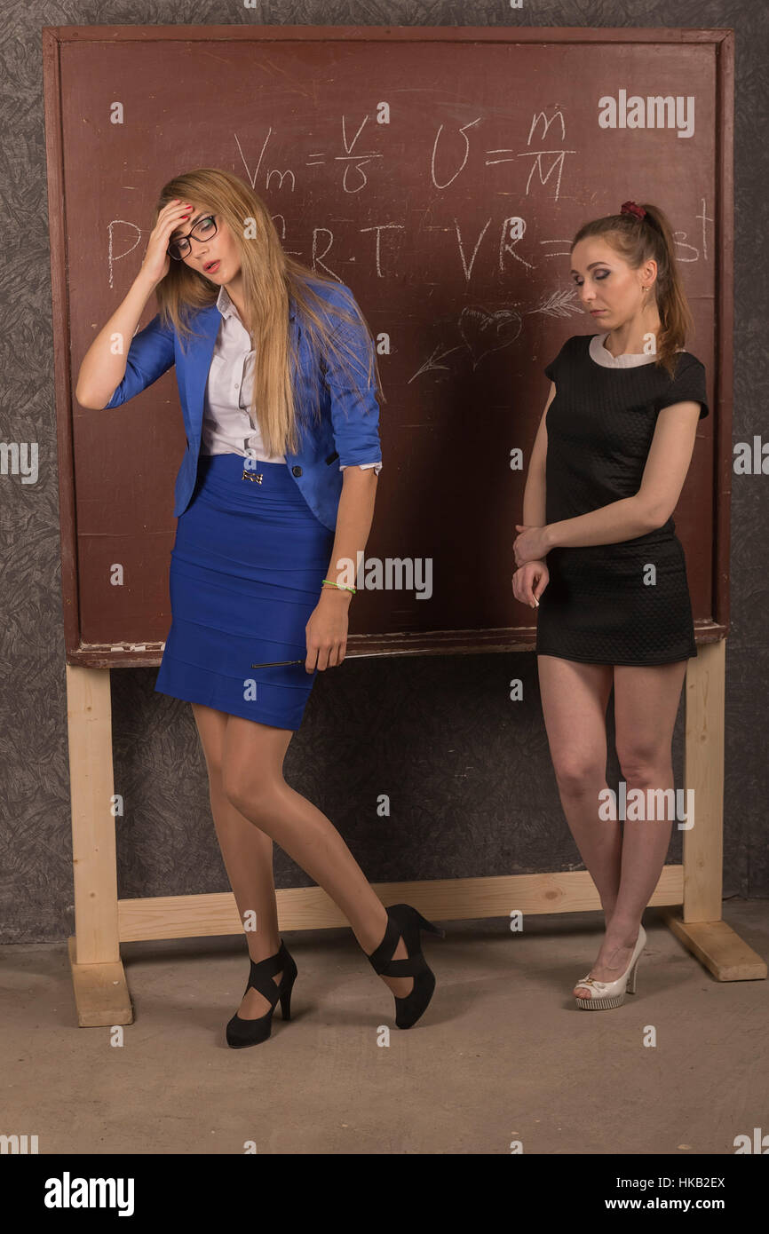 Woman teacher in a daring outfit and embarrassed the student in front of the old school board. - Stock Image