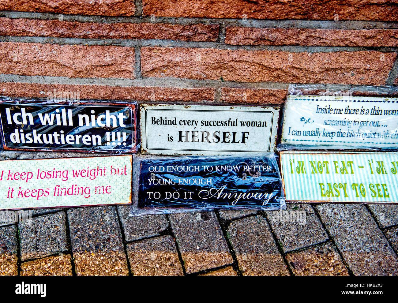 Funny sayings on plates on display; humorvolle Sprüche auf ausgestellten Metallplatten vor einem laden - Stock Image