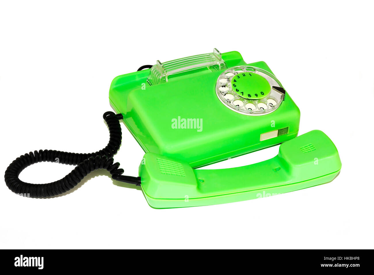 On a white background is an old telephone with a round dialer - Stock Image