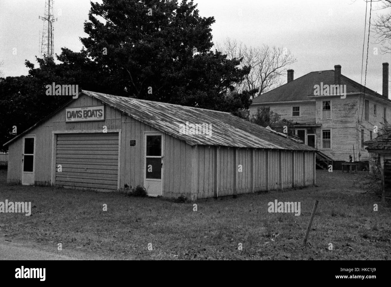 Grainy black and white photo of a boat repair barn behind a house on the Outer Banks in the town of Manteo NC. - Stock Image