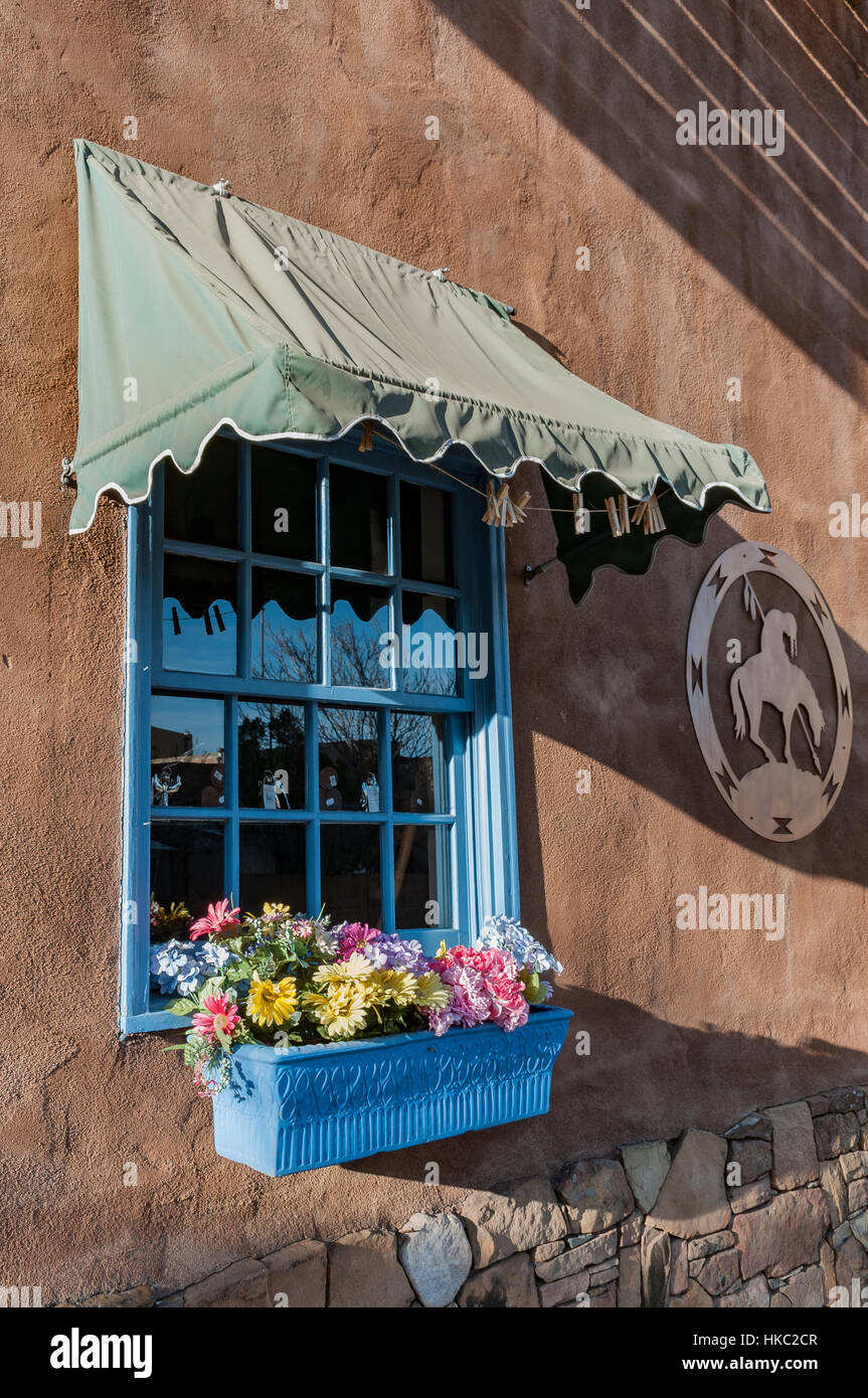 A blue window with a flower-filled window box in an adobe building in Old Town, Santa Fe, New Mexico. - Stock Image