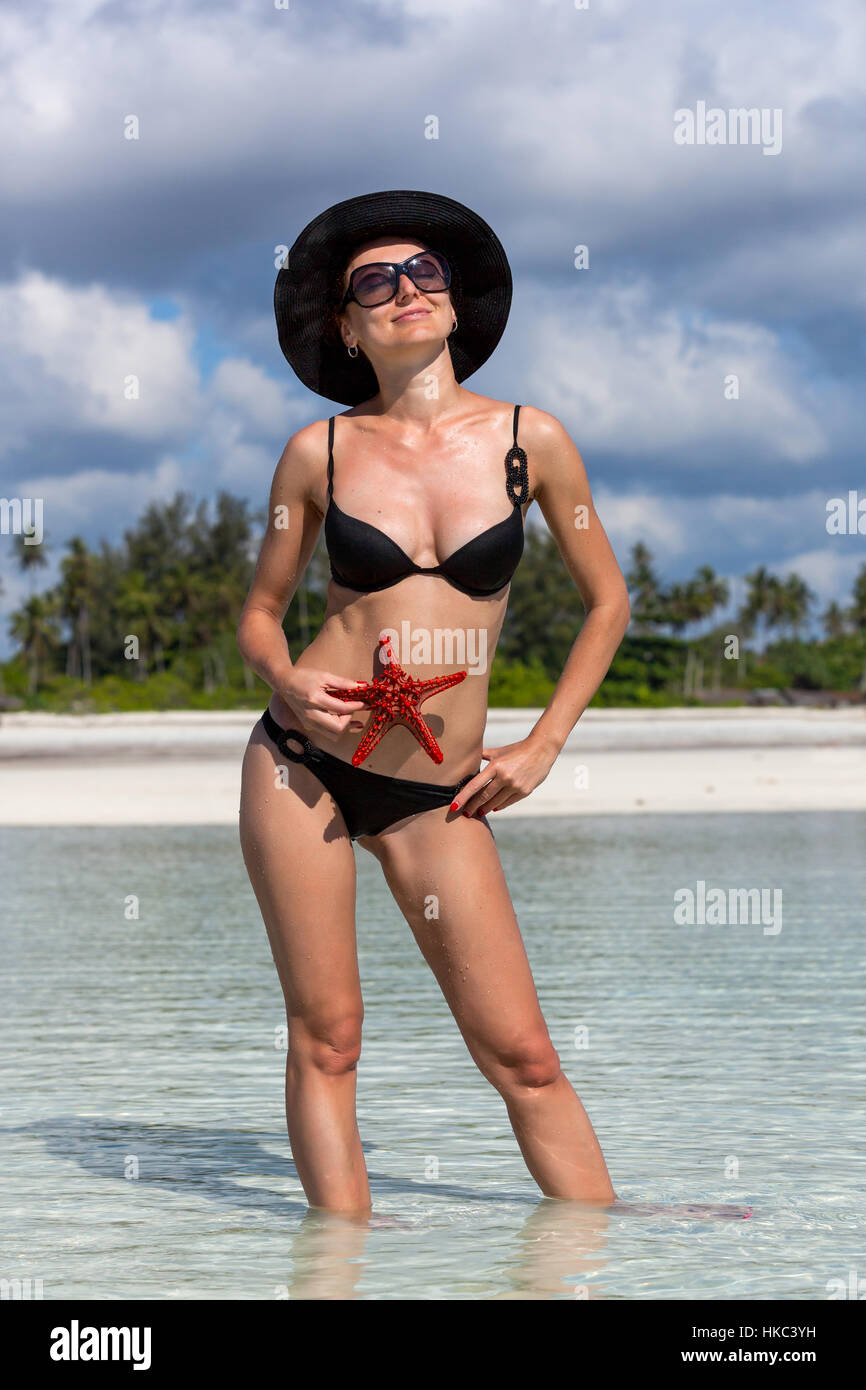 Girl holding a starfish against some exotic island,Seaside acquaintance - Stock Image
