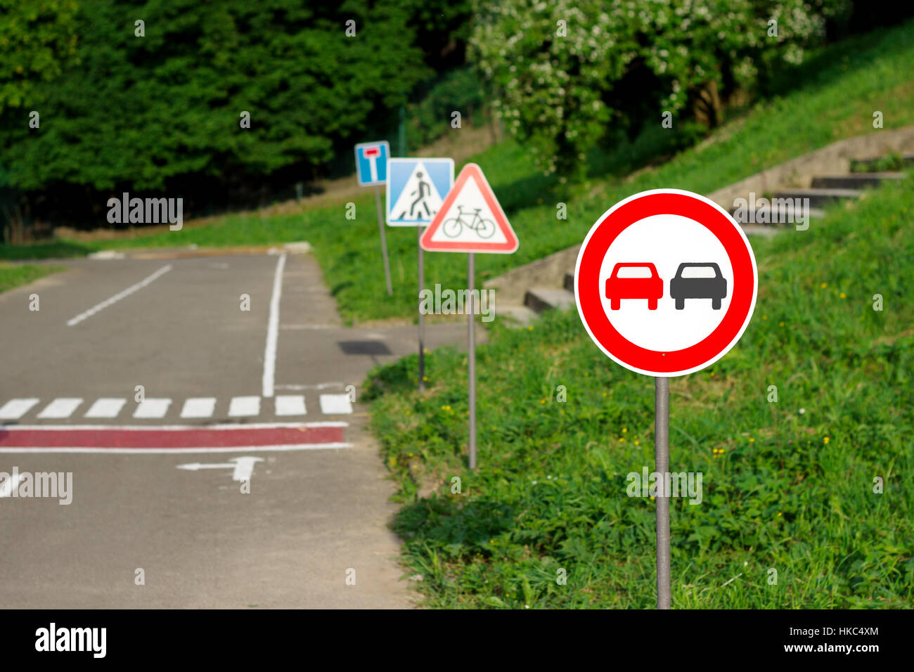 no overtaking, no passing, cyclists, pedestrians, dead end signs on the training kids track in the park - Stock Image