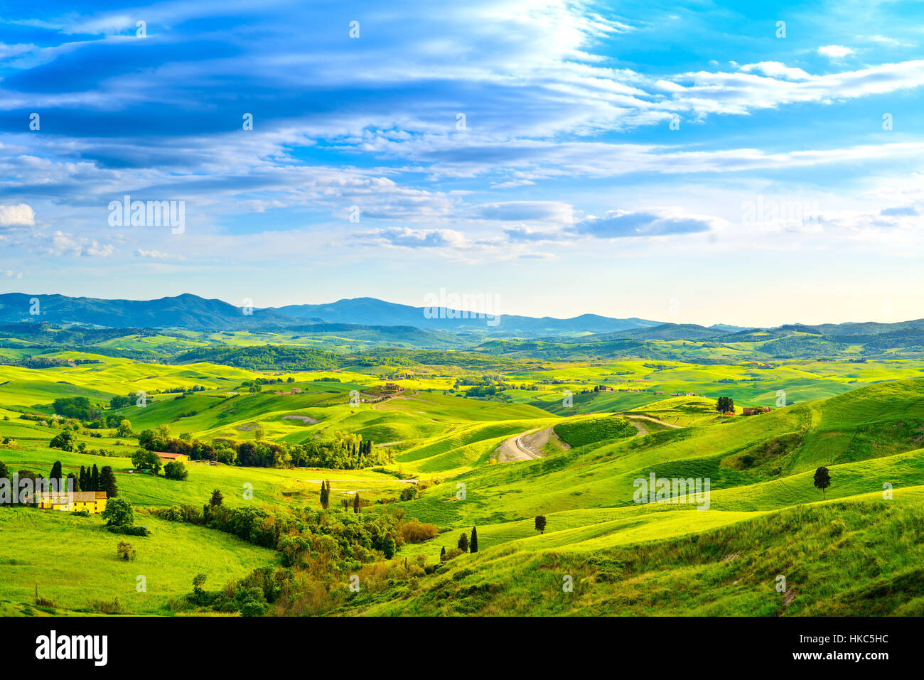 Tuscany, rural sunset landscape. Countryside farm, cypresses trees, green field, sun light and cloud. Volterra, - Stock Image