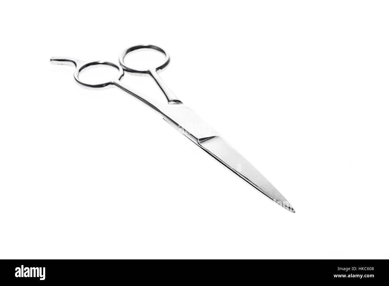 Hairdresser or barber silver professional scissors for cutting hair. Isolated on white background - Stock Image